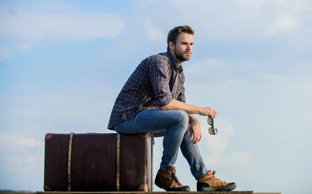 Adventure is out there. man sky background. male fashion style. looking so trendy. businessman in glasses. business trip. macho man unshaven face sit on tour bag. traveler wait for flight. Move