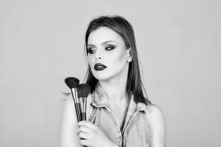 Emphasize femininity. Girl apply powder eye shadows. Looking good and feeling confident. Makeup dark lips. Attractive woman applying makeup brush. Professional makeup supplies. Makeup artist concept