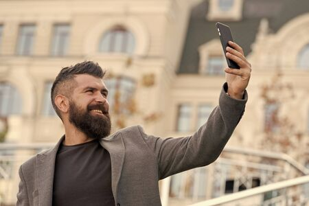 Man smiling taking selfie photo smartphone urban background. Streaming online video call. Mobile internet. Hipster mobile phone. Blog content. Personal blog. Modern life. Mobile internet