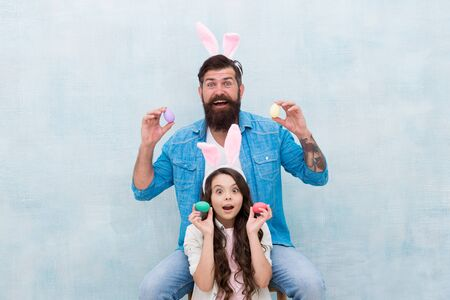 Spring mood. easter family party. happy easter concept. father and daughter collect pained eggs. egg hunt is right now. having fun in rabbit costume. dad and child wear bunny ears 版權商用圖片