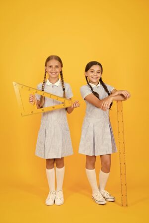 smart children at stem lesson. girls love geometry. old school. modern education. happy friends in retro uniform. vintage kid fashion. back to school. small girls hold math tools. STEM disciplines