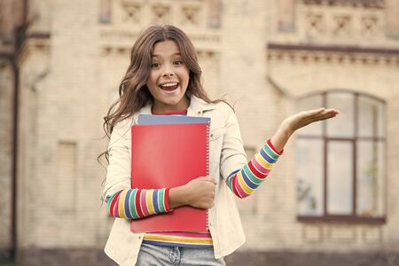 Successful pupil. Taking extra course for deeper learning. School education. Modern education. Kid smiling girl school student hold workbooks textbooks for studying. Education for gifted children