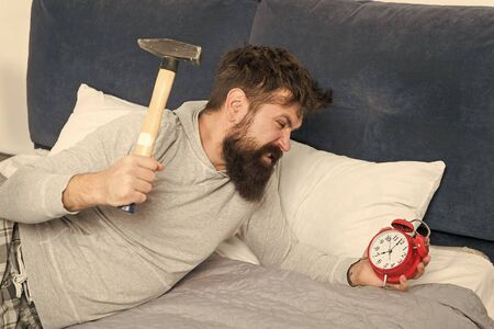 this is monday. hate noise of alarm clock. Irritated guy destroy annoying clock. Man awake unhappy with alarm clock ringing. Sleep longer. Healthy sleep concept. bearded man hipster want to sleep