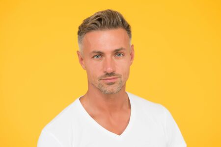Taking care of your hair. Unshaven guy yellow background. Handsome man with short facial hair. Skin care routine. Skincare. Barbershop. Mens grooming and care. Stubble face care products