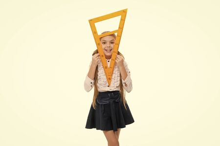 Girl with big ruler. Favorite school subject. Education and school concept. School student learning geometry. Kid school uniform. STEM concept. Learn theorem about right angle. geometric shapes 版權商用圖片