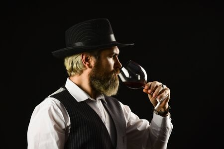elite drink. Checking color and sediments of wine. Wine tasting. Male skilled sommelier estimates alcoholic drink. red wine in long-stemmed wineglasses. bearded man explore taste of in restaurant