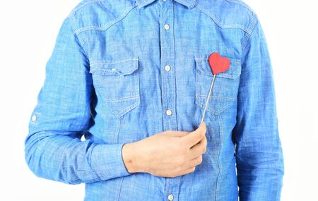 Paper red heart on blue male shirt.