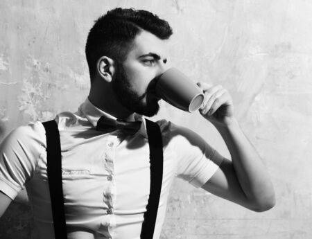 bearded man, long beard, brutal caucasian hipster with moustache in white shirt and suspenders with bow-tie drinking from blue cup of tea or coffee with serious face on background of wall Banque d'images