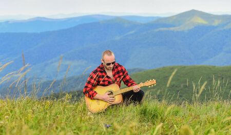 music speaks. man with guitar in checkered shirt. hipster fashion. western camping and hiking. happy and free. cowboy man with acoustic guitar player. country music song