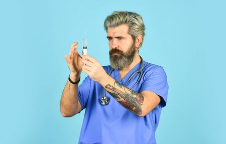 Antidote. Man nurse with coronavirus vaccine in syringe. Flu vaccine. Bearded doctor wear uniform use syringe needle vaccination. Dose injection. Medical injection. Vaccine development. Innovation