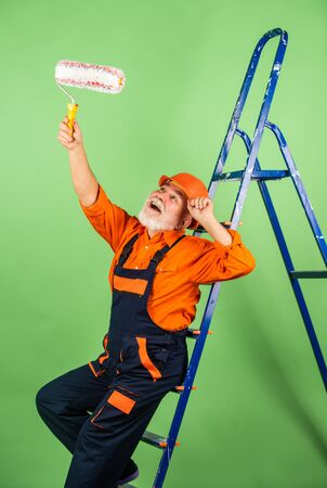 Painter man staircase. To make repairs. man in working clothes painting wall in empty room. painter in overall and cap with paint bucket. builder worker painting facade. thermal insulation works.