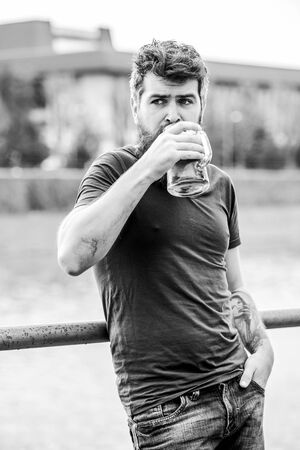 Guy having rest with cold draught beer. Hipster relaxed drinking beer outdoor. Cafe summer terrace. Light ales or dark stouts drink them all. Man with beard and mustache hold beer glass outdoors