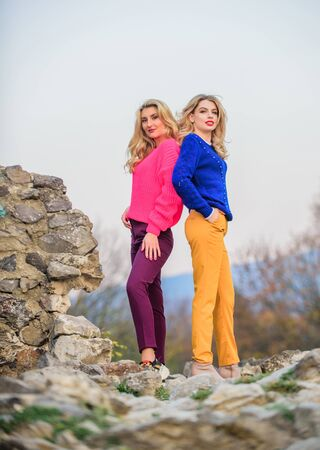Vivid style concept. Sisters enjoy colorful outfits on gloomy day sky background. Bright mood. Bright sweaters and pants increase activity add cheerfulness and improve mood. Girls wear bright clothes