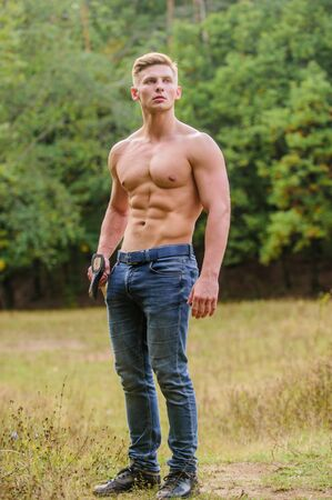 full of energy. brutal and attractive male in wood. bodybuilder show his muscles. power and strength. lumberjack carry axe. man strong body. muscular man with axe. macho torso ax Standard-Bild