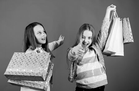 Shopping day happiness. Happy children in shop with bags. Sisters shopping together. Buy clothes. Fashionista addicted buyer. Fashion boutique kids. Shopping is best therapy. Shopping of her dreams Stock Photo