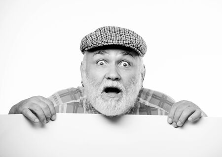 Announcement concept. Event announcement. Senior bearded emotional man peek out of banner place announcement. Pensioner grandfather in vintage hat poster information copy space. Elderly person