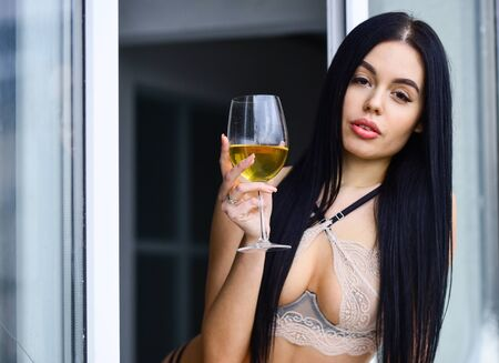 After party. Fashion lady enjoy luxury lifestyle. elite lingerie. Beautiful girl body in lingerie bra. beauty tasting wine. woman in lingerie holding a glass of wine. Arrogance and provocation Foto de archivo