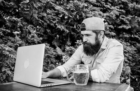 Computer technology makes life easier. Hipster drinking beer and using laptop technology outdoor. Bearded man communicating through communication technology. Modern technology