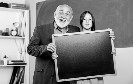 A Better Way Found. mature teacher and happy pupil girl. small girl with man tutor study. blackboard for information and announcement. Copy space. school classroom. empty chalk board. School sales