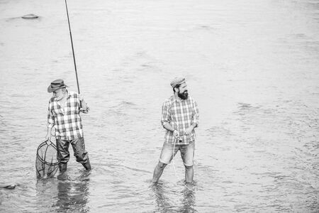 Fishing team. Male friendship. Father and son fishing. Summer weekend. Happy fisherman with fishing rod and net. Hobby and sport activity. Fishing together. Men stand in water. Nice catch concept