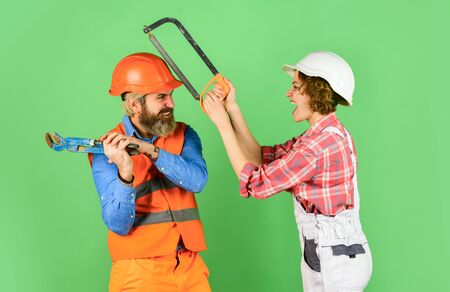 having fun. imagine their new house. Portrait of confident handyman and his female colleague. follow repairing steps. wear special uniform and use tools. Maintenance service. building concept