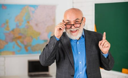 idea and inspiration. become good at geography. senior man teacher at blackboard. bearded tutor in glasses near geography map. back to school. lesson in classroom. learn geography easily