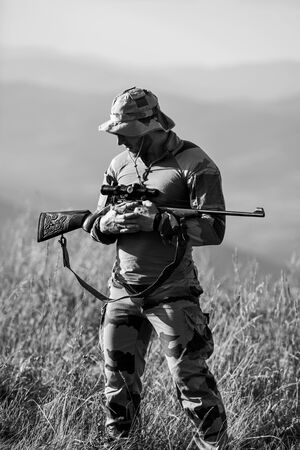 Army forces. Man military clothes with weapon. Brutal warrior. Rifle for hunting. Ready to shoot. Hunter hold rifle. Hunter mountains landscape background. Focus and concentration experienced hunter