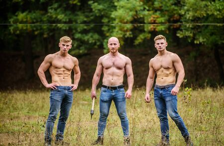 Bandit gang and conflict. relax after work in the forest. three muscular men with axe. athletic man use ax. brutal and strong male. sexy guys six packs and biceps. protein or steroids. bodybuilding Banque d'images