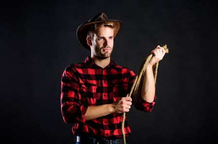 Brutal and confident. Western life. Man unshaven cowboy black background. Man wearing hat hold rope. Lasso tool of American cowboy. Lasso used rodeos competitive events. Lasso can be tied or wrapped