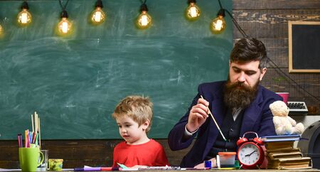 Child and teacher on busy faces painting, drawing. Arts lesson concept. Teacher with beard, father and little son in classroom while drawing, creating, chalkboard on background. Banque d'images - 142218838