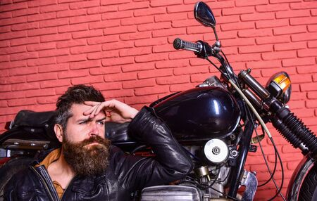 Bikers lifestyle concept. Hipster, brutal biker on pensive face in leather jacket sits, leans on motorcycle. Man with beard, biker in leather jacket near motor bike in garage, brick wall background. 스톡 콘텐츠