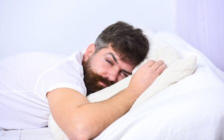 Man in shirt laying on bed, white wall on background. Macho with beard and mustache sleeping, relaxing, having nap, rest. Guy on tired face sleeping on white sheets and pillow. Nap and siesta concept.
