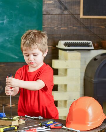 Concentrated kid binding screw to wooden board with both hands. Blond boy working in repairs workshop. Preschooler gaining new skills