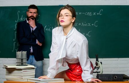 Attractive teacher in leather skirt. Cheeky teacher. Impudent student. Science is sexy. Sexy girl sit table while man stand chalkboard. Flirting with colleague. Everyone dreaming about such teacher Фото со стока