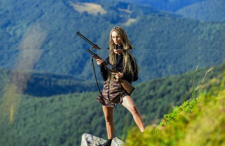 Sexy warrior. Woman attractive long hair pretty face hold rifle for hunting. Amazon legendary race of female warriors. Hunting season. She is warrior. Warrior mountains landscape background
