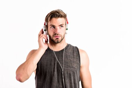 sport music. joy and relax. sexy muscular man listen sport music. man in headset isolated on white. unshaven man in blue tooth headphones. Enjoying favorite music