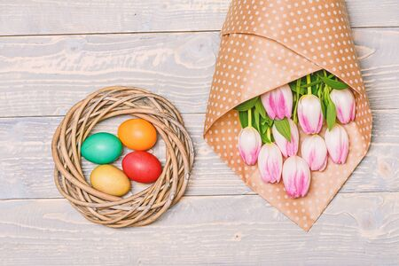 painted eggs in nest. Spring holiday. Holiday celebration, preparation. Happy easter. Tulip flower bouquet. Healthy and happy holiday. Egg hunt. Nice bouquet.