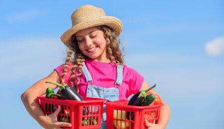 Selling homegrown food concept. Natural vitamin nutrition. Organic vegetables. Girl cute child farming. Gathering vegetables in basket. Village rustic style. Vegetables market. Sunny day at farm Standard-Bild