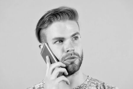 Bearded man talk on mobile phone. Macho use smartphone. Guy with mobile device. Digital marketing, buy online and cyber monday concept. New technology for communication and modern life. Stockfoto