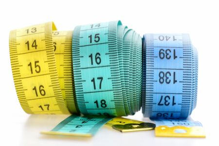 Weight loss and sport concept. Yellow and blue rolled tapes isolated on white background. Three rolled centimeter rulers. Tapes for measuring waist and figure with indicators in form of centimeters. Stockfoto