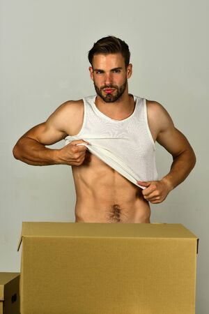 Man with sexy body getting dressed with serious look Stock Photo