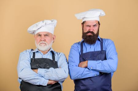 Made right choice. professional chef. serious men in cook hat. mature bearded chef. tired of cooking. who is the best. family dinner. father and son cooking together. commercial kitchen at restaurant 版權商用圖片
