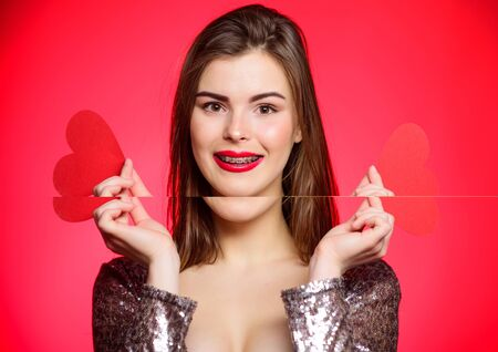 Valentines day concept. Braces and beauty. Dating when you have adult braces. Girl pretty wearing orthodontic braces and smiling. How to kiss with braces. Woman makeup red lips hold heart symbol love
