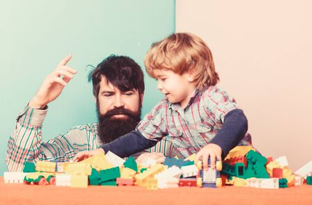 happy little boy with bearded man dad playing together. father and son play game. building home with colorful constructor. happy child development. happy family. leisure time. feeling happy Standard-Bild