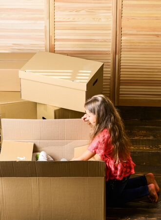 look inside. happy child cardboard box. repair of room. new apartment. unpacking moving boxes. purchase of new habitation. Cardboard boxes - moving to a new house. happy little girl in room on boxe
