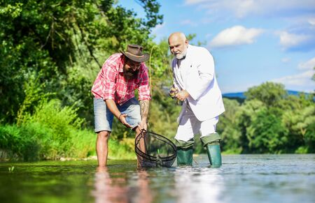 Family bonding time. fly fish hobby of businessman. retirement fishery. retired dad and mature bearded son. Two male friends fishing together. happy fishermen friendship. Catching and fishing concept