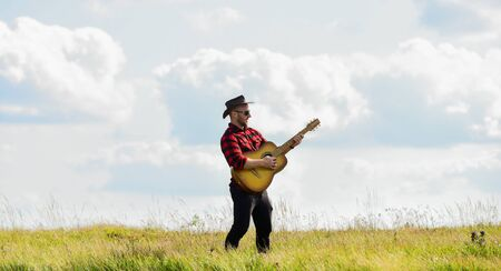 music begins. man with guitar in checkered shirt. western camping and hiking. hipster fashion. happy and free. cowboy man with acoustic guitar player. country music song