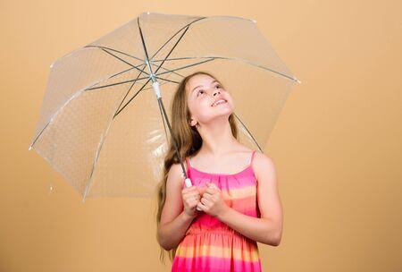 Seasonal changes. Fall season. Enjoy rain concept. Waterproof accessory. Rainy days coming. Love rainy days. Kid girl happy hold transparent umbrella. Enjoy rainy weather. Invisible protection 版權商用圖片
