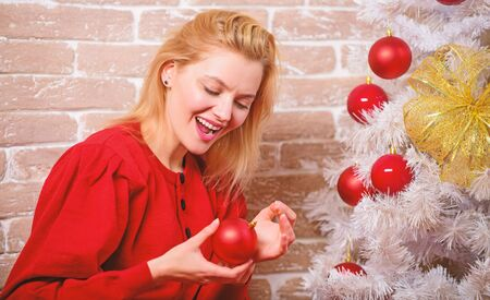 Waiting for christmas. Woman happy relaxing near christmas tree. Things you must do before holiday celebration start. Christmas eve concept. Girl in red dress decorate christmas tree with ornaments