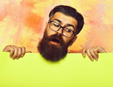 bearded man with surprised face in glasses on colorful background